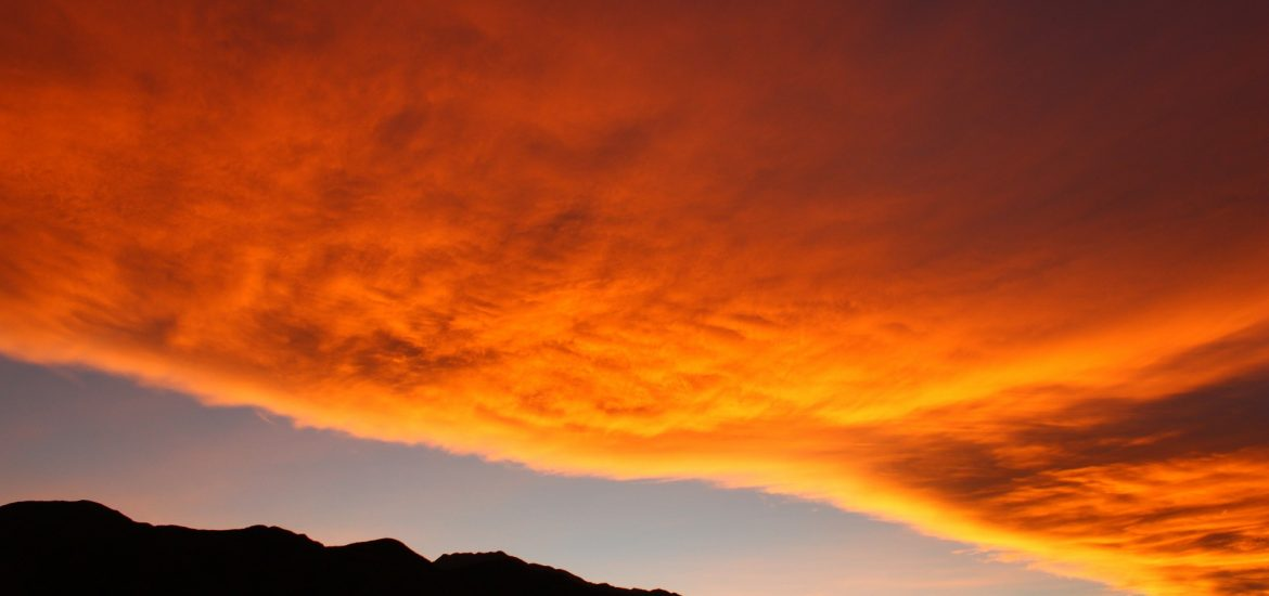 Blazing sunset colors in clouds over mountain ridge