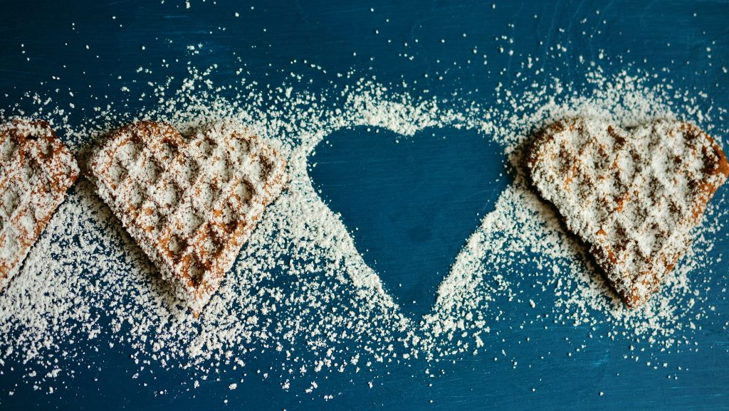 3 heart shaped waffles sprinkled with powdered sugar